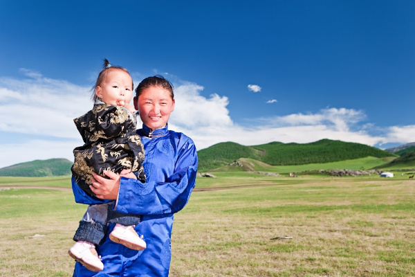 mongolian mother and baby standing outside of their ger